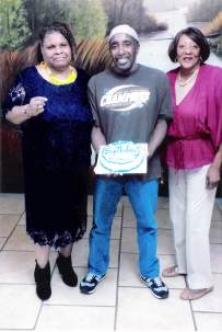 Photo of Zulu holding a birthday cake with his sisters